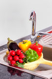 Vegetables near to steel faucet Royalty Free Stock Images