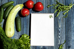 Vegetables and notepad on wooden desk Royalty Free Stock Image