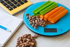 Vegetables and nuts on the scales. Calorie counting Stock Images
