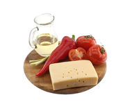 Vegetables, oil and cheese on cutting board, isolated on white Royalty Free Stock Image