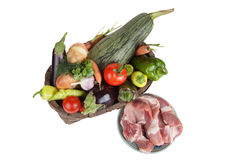 Vegetables in old wooden basket and fresh meat isolated on white Royalty Free Stock Images