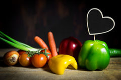 Vegetables on a old wooden table with a heart with copyspace Stock Photography