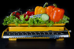 Vegetables on an old yellow kitchen scale Royalty Free Stock Photos