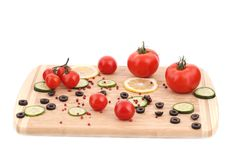 Vegetables and olives on cutting board. Stock Photos