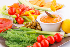 Vegetables, olives, nachos, red and cheese sause Stock Image