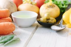 Vegetables, olives and spices over white wooden table. royalty free stock photo