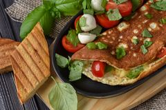 Vegetables omelette with tomatoes, basil, mozzarella, toast. Rus. Tic Royalty Free Stock Images