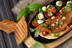 Vegetables omelette with tomatoes, basil, mozzarella, toast. Rus. Tic Stock Photo