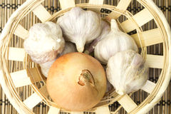Vegetables. Onion and garlic on a wooden napkin closeup Stock Images