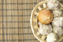 Vegetables. Onion and garlic on a wooden napkin closeup Stock Image