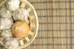 Vegetables. Onion and garlic on a wooden napkin closeup Stock Photos