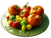 Vegetables from our garden. Home grown tomatoes, red and yellow, figs and red pepper on a green porcelain plate. Isolated Stock Image