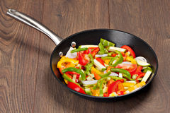 Vegetables in the pan. On the wooden table Royalty Free Stock Photo
