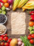 Vegetables, paper and chickpea on a wooden table Royalty Free Stock Images
