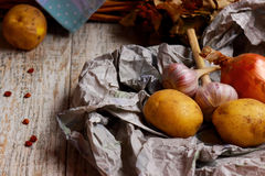 Vegetables in paper. Vegetable still life - potatoes, garlic, onions in a paper bag Stock Images