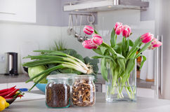 Vegetables and pink tulips on table in the kitchen royalty free stock photography