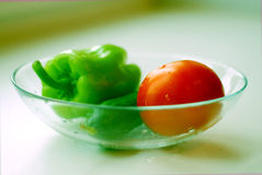 Vegetables on a plate. Green and red vegetables on a glass plate - pepper, cucumber and tomato. With green ambient light stock image