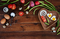 Vegetables and a plate with fried eggs on wooden background overhead close up shoot Royalty Free Stock Photo