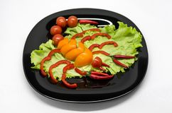 Vegetables on a plate laid out in the shape of a scorpion royalty free stock photography