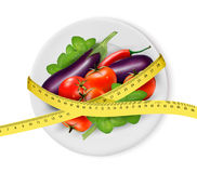 Vegetables on a plate with measuring tape. Dieting concept. Stock Photos