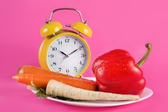 Vegetables on a plate and retro alarm clock isolated on pink background stock photography
