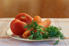 Vegetables on a plate. Tomatoes, carrots, coriander and dill on a transparent plate on a table Stock Image