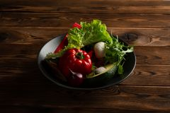 Vegetables in the plate on wooden background stock photos