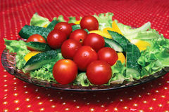Vegetables on a platter. Fresh vegetables on a crystal dish on the table with a red cloth Royalty Free Stock Photo