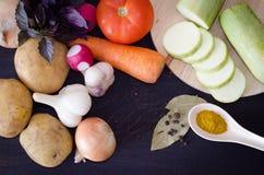 Vegetables potato, tomato, onion, garlic and zucchini slices and radish, spices. On black background Stock Photo