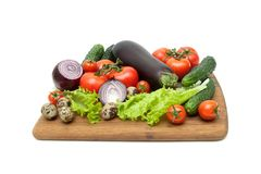 Vegetables and quail eggs on a cutting board on a white backgrou Royalty Free Stock Photo