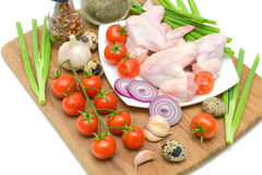 Vegetables and raw chicken wings closeup. Vegetables, quail eggs and raw chicken wings close-up. horizontal photo Stock Photography