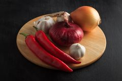 Vegetables red pepper, onions and garlic on a wooden stand Royalty Free Stock Photography