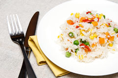 Vegetables risotto. Boiled rice with green peas, corn, sweet peppers and carrots on a white plate Royalty Free Stock Images