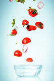 The vegetables for salad falling on blue Royalty Free Stock Photography