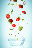 The vegetables for salad falling on blue Royalty Free Stock Image