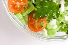 Vegetables salad in a glass salad bowl. Over white background royalty free stock images