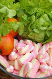 Vegetables salad, tomato and pink marshmallows. Royalty Free Stock Photo