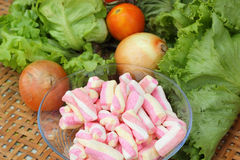 Vegetables salad, tomato and pink marshmallows. Stock Photos
