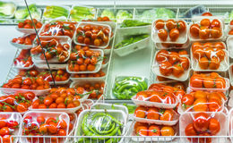 Vegetables for sale. Closeup inside an Italian supermarket with large quantities of tomatoes, a classic food for the Mediterranean cuisine Royalty Free Stock Image