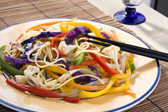 Vegetables sauteed. Close up of a vegetables sauteed dish. Red, yellow and green pepper, cabbage, cauliflower, carrots and spaghetti. Focus around chopsticks Royalty Free Stock Images