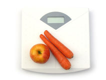 Vegetables on scale. Carrots and red apple on a white bathroom scale. Blank display Stock Images