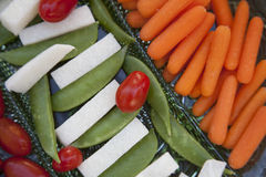 Vegetables served as horderves before dinner. Plated carrots, tomatoes, jimaca and snap peas as a before dinner snack Royalty Free Stock Image
