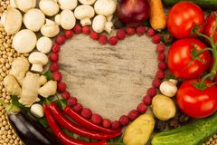 Vegetables in the shape of a heart on wooden background, vegetarian food. Stock Images