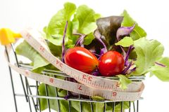 Vegetables in the shopping cart with measuring tape on white background. For healthy food concept stock photos