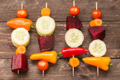 Vegetables skewers on the wooden background. / the concept of healthy lifestyle Stock Photos