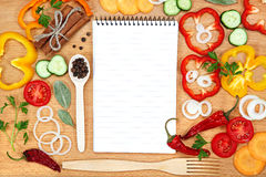 Vegetables, spices and notepad for recipes, on table. Stock Photo