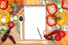 Vegetables, spices and notepad for recipes, on wooden table Stock Photos