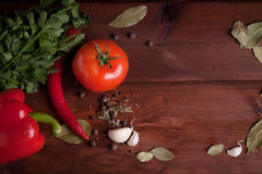 Vegetables and spices on wood desk. Red wet tomato, red pepper and chili pepper with herbs and spices on wood desk Stock Image