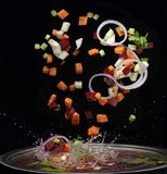 Vegetables splash in soup cooking concept stock photos