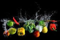 Vegetables splash in water. On black background stock photo